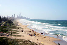 A beach sloping down from a grassy area on the left to the sea on the right, a city can be seen in the horizon