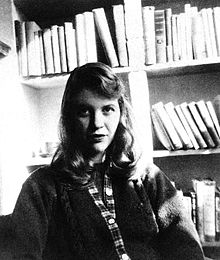 A black-and-white photo of a Caucasian woman with shoulder-length hair. She is seated facing the camera, wearing a sweater, with bookshelves behind her.