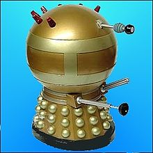 Image of a squat Dalek, painted overall in gold. It has brass-coloured hemispheres, collars and two wide bands around the spherical head section, the upper rear portion of which is adorned with seven red lights.