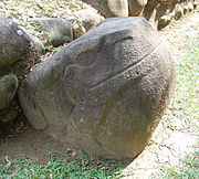 A smoothly finished boulder carved into the shape of a seated frog or toad, with the head raised to the right and sporting a prominent smile. The eyes, mouth, nostrils and legs are all carved in low relief. The sculpture is set against the stonework base of a structure, behind it at left.