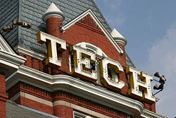 """Large, white, capital letters spelling """"TECH"""" situated just below the pointed roof of the square, red brick tower of the administration building"""