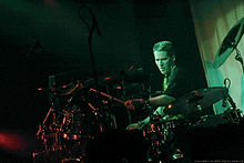 Drummer with crewcut, wearing black t-shirt, intently plays his large drum set in the spotlight.