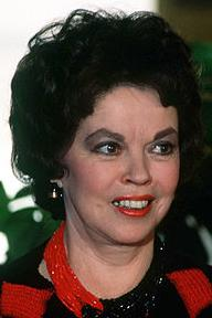 Head shot of Temple as an adult. She is smiling and wearing a top and beaded necklace, both red and black.