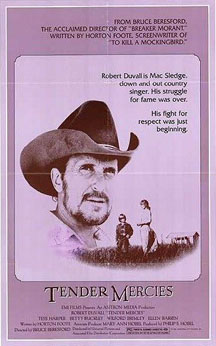 """A movie poster with a large picture of a bearded man wearing a cowboy hat, suspended in the background of a photo of a much smaller scaled woman and young boy talking in a field. A tagline beside the man reads """"Robert Duvall is Mac Sledge, down and out country singer. His struggle for fame was over. His fight for respect was just beginning."""" At the bottom, the words """"Tender Mercies"""" appear, along with much smaller credits text. The top of the poster includes additional promotional text."""
