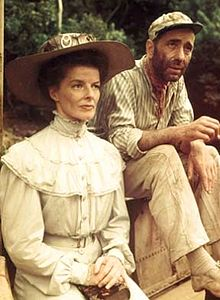 Hepburn is dressed in early 20th century clothes, looking prim and proper. Behind her is Humphrey Bogart, also dressed as his character from The African Queen.