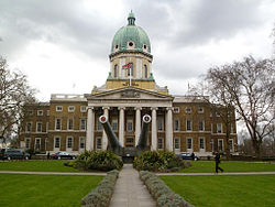 A three-storey brick building with tall copper dome on top, a frontage of six Doric columns and portico, and in front of the columns two large naval guns with  tampion badges on a concrete base.