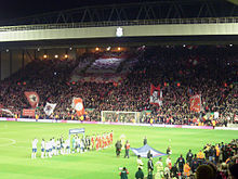 A stand which is full of people set behind a field of grass. There are a number of flags and banners in the crowd. On the field of grass are a number of people.