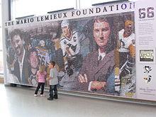 Mur de mosaïque représentant plusieurs images de Mario Lemieux surmontées des mots The Mario Lemieux fondation.