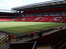 """A two-tiered stand which has red seats, there are also white seats which spell out """"L.F.C. In front of the stand is a field of grass"""