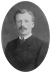 Headshot photo of a young man, similar in appearance to his brother, but neat, well-groomed and calm.