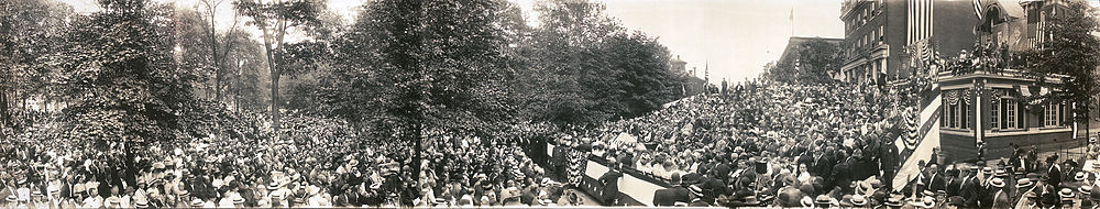 A panorama image showing a large crowd seated in chairs and standing outdoors around a speaker who delivers a speech on a podium in the center. Downtown brick buildings and large campaign posters are in the background.