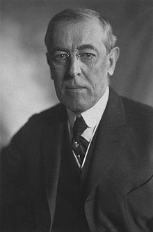Half-length portrait of a man wearing a three piece suit, a neck tie, round rimmed glasses and looking directly towards the photographer with an emotionless expression.