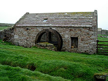 La photo montre un bâtiment en pierre d'un âge certain. Au milieu du bâtiment se trouvent les restes d'une roue en bois.