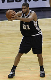 A man of lighter complexion holds a basketball while playing in a basketball game.
