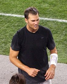 A man standing on the sidelines of an American football field. He is wearing a black shirt.