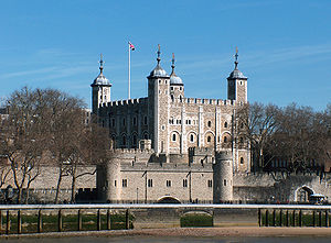 A keep seen from a river, rising behind a gate. The keep is large, square in plan, and has four corner towers, three square and one round, all topped by lead cupolas