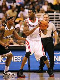 """A basketball player, wearing a white jersey inscribed with the word """"ROCKETS"""" across the front, holds a basketball away from another basketball player guarding him. A referee stands in the background."""