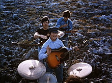 The Beatles performing music in a field. In the foreground, the drums are played by Starr (only the top of his head is visible). Beyond him, the other three stand in a column with their guitars. In the rear, Harrison, head down, strikes a chord. In the front, Lennon smiles and gives a little wave toward camera, holding his pick. Between them, McCartney is jocularly about to choke Lennon.