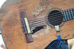 A classical guitar. There are several damages in the soundboard, near the sound hole there is a big hole and the wood is worn out in the surrounding areas of it. The guitar has several signatures on it. there is a blue and white strap in the soundhole.