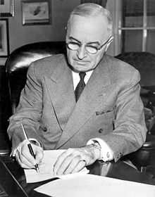 Man in gray suit and glasses signing a document