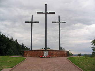 A Memorial consisting of three crosses standing on a large brick pedestal. Each cross bears a name - Katyn, Kharkiv, or Mednoye.