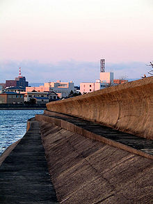 Photo of seawall with building in background