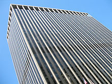 Street view of top half of skyscraper against the sky; its outside is dominated by vertical black and white lines