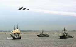 Photo of a ship at sail with two escorts as navy jets fly overhead