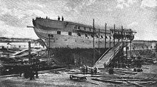 A photograph of a ship out of the water and under repair