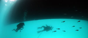 Two divers under a ship
