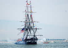 A photo of a ship without sails. There is white cannon smoke emitting from the left and right sides of the ship. A tugboat is alongside