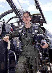Une femme en uniforme de pilote devant le cockpit ouvert d'un avion de chasse