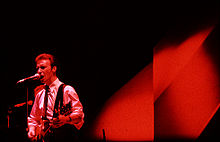 A colour photograph of members of Midge Ure of the band Ultravox performing on a stage with a microphone and a guitar