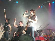 A rock band on stage wearing black or white t-shirts and jeans, in the spotlight performing before an audience.