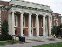 A large Georgian-style building exterior with six Ionic Columns and red brick with large arched windows
