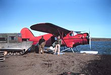 Two men standing facing camera under the wing of a red float plane. Some parcels of cargo are visible in the hatch, and a large tracked snow machine is parked on the left.