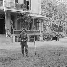 Man standing in front of imposing house with a pennant of a flag pole beside him