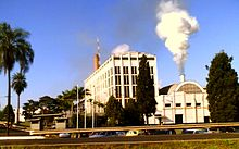 Photo of shorter building with smoke coming out of smokestack next to five-story office building