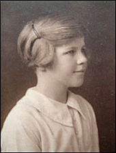 Head-and-shoulders photograph of a young girl. She wears a light-coloured blouse and faces right, looking out of the picture, with a slight smile. Her short hair is pulled back from her face and pinned up.