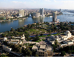 A sharp blue river divides the cityscape, which is primarily greenery and sparse low-rise buildings in the foreground, and dense with several modern high-rises in the background