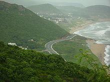 Aerial view of two-lane highway, surrounded by forest and beach