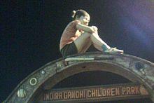 Child sitting atop playground apparatus