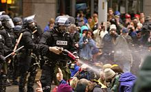 A law enforcement agent sprays pepper spray at the crowd.