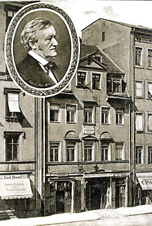 A postcard of a five-story building with shops on the ground floor and garret windows in the roof. A round inset has a picture of Wagner in middle age.