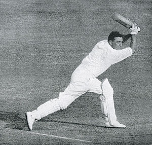 A dark haired man wearing a white shirt, white trousers and cricket pads, holds a cricket bat in the air having just played a shot.