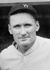 """A man in a white baseball jersey and a dark baseball cap with """"W"""" on it."""