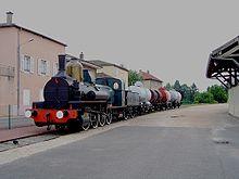 La photo couleur représente une locomotive à vapeur bleu attelée à des wagons citernes et bifoudres.