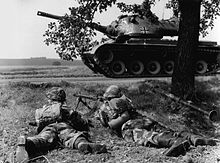 Two soldiers crouch under a tree while a tank sits on a road in front of them.