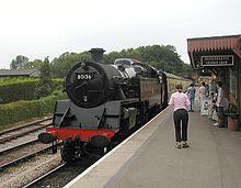 Station platform with black locomotive.