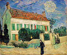 A white two story house at twilight, with 2 cypress trees on one end, and smaller green trees all around the house, with a yellow fence surrounding it. Two women are entering through the gate in the fence; while a woman in black walks on by going towards the left. In the sky, there is a bright star with a large intense yellow halo around it